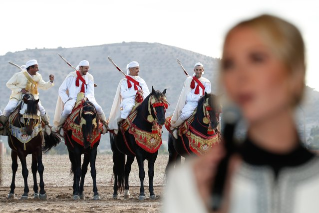 Moroccans in traditional costumes ride horses while Ivanka Trump, the daughter and senior adviser to President Donald Trump speaks during a ceremony in the province of Sidi Kacem, Morocco, Thursday, November 7, 2019, at an olive grove collective where Trump met with local women farmers who are benefitting from changes allowing them to inherit land. (Photo by Jacquelyn Martin/AP Photo)