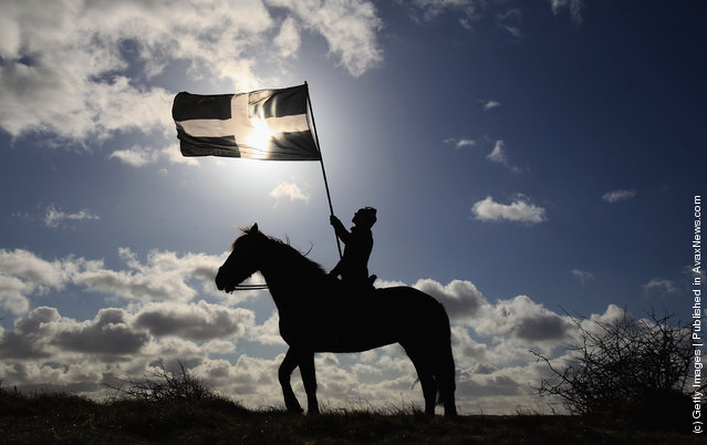 A woman on horseback flies the flag of Cornwall during the annual processional play to celebrate St Piran, patron saint of tinners and regarded by many as Cornwall's premier saint