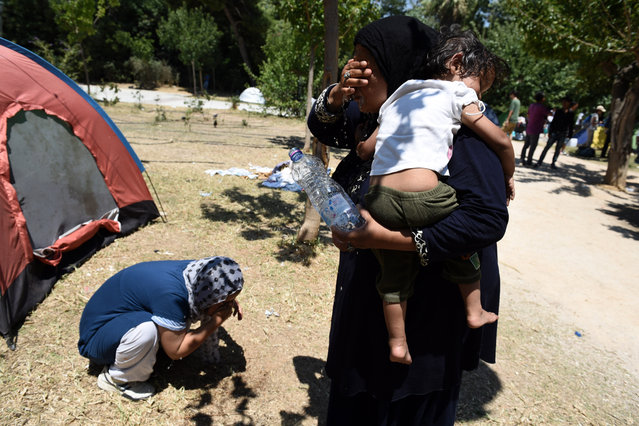 Afghan refugees cool down in the Pedion tou Areos park in central Athens, on Friday, July 24, 2015. (Photo by Giannis Papanikos/AP Photo)
