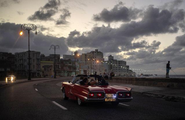 In this November 10, 2019 photo, tourists take a joy ride along the malecon sea wall in Havana, Cuba. (Photo by Ramon Espinosa/AP Photo)