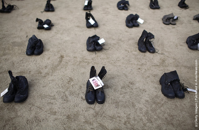 A photograph is displayed on a pair of combat boots that are part of the Eyes Wide Open exhibit in front of San Francisco City Hall