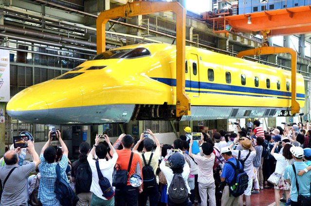 """""""Dr. Yellow"""", a high-speed test train, is lifted at JR Hamamatsu factory of JR Tokai during periodic inspection, Hamamatsu, Shizuoka Prefecture on July 25, 2015, as a crowd of train spotters are taking pictures. This is the first opportunity for the public people to see the belly of the Shinkansen bullet train. (Photo by The Yomiuri Shimbun via AP Images)"""