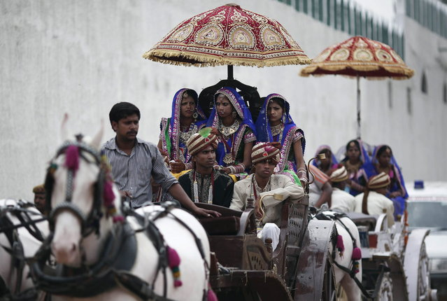 Brides and grooms arrive in horse carts to attend a mass wedding ceremony at Ramlila ground in New Delhi June 15, 2014. A total of 92 physically challenged couples of all religions from across India took their wedding vows on Sunday during the mass wedding ceremony organised by a non-governmental organisation (NGO), organisers said. (Photo by Adnan Abidi/Reuters)
