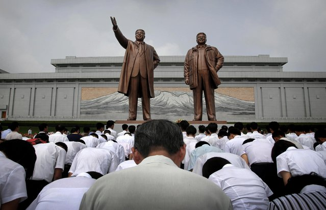 North Koreans bow in front of bronze statues of the late leaders Kim Il Sung and Kim Jong Il at Munsu Hill, Monday, July 27, 2015, in Pyongyang, North Korea. (Photo by Wong Maye-E/AP Photo)