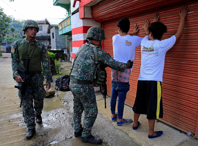 A government soldier frisks a resident who evacuated his home in Sarimanok village, Marawi City, Philippines June 1, 2017, during an ongoing assault of government troops on insurgents from the Maute group, who have taken over large parts of the city. (Photo by Romeo Ranoco/Reuters)