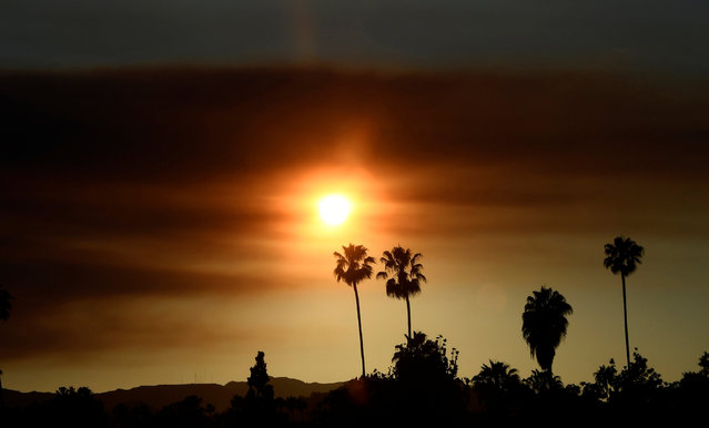 """As seen from the San Fernando Valley of Los Angeles, the sun set behind a smokey sky caused by the """"Old Fire"""", which burned in Calabasas, California, U.S., June 4, 2016. (Photo by Gene Blevins/Reuters)"""