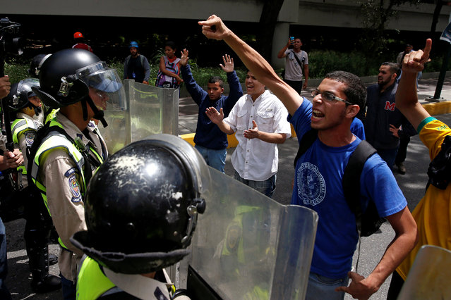 Demonstrators shout slogans in front of riot policemen during a protest called by university students against Venezuela's government in Caracas, Venezuela, June 9, 2016. (Photo by Carlos Garcia Rawlins/Reuters)