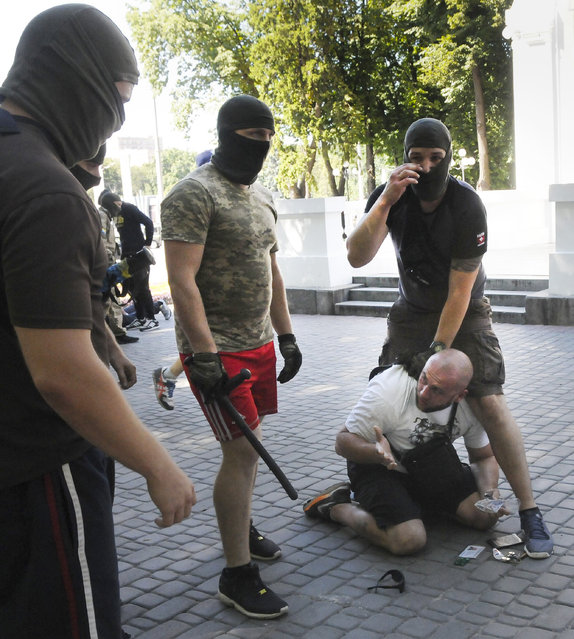 Ukrainian plain clothed policemen arrest a pro-Russian activist after mass violence in Ukraine's border city of Kharkiv Monday, August 3, 2015. The police have opened a criminal investigation after violence occurred near the office of the Opposition Bloc. (Photo by AP Photo/Stringer)