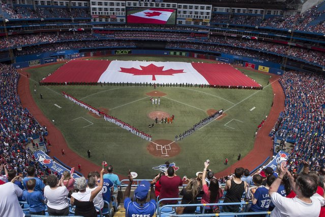 A Canadian flag is unveiled on the field before the Toronto Blue Jays take on the Milwaukee Brewers in interleague baseball action as they mark Canada Day in Toronto on Tuesday July 1, 2014. (Photo by Chris Young/The Canadian Press)