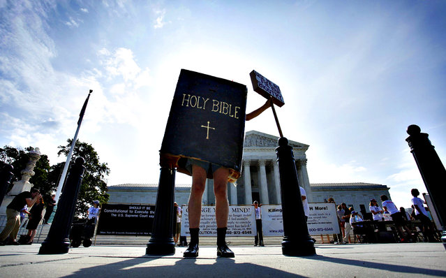 A protester dressed as a copy of the Bible joins groups demonstrating outside the U.S. Supreme Court in Washington June 30, 2014. The U.S. Supreme Court on Monday ruled that business owners can object on religious grounds to a provision of U.S. President Barack Obama's healthcare law that requires closely held companies to provide health insurance that covers birth control. (Photo by Jonathan Ernst/Reuters)