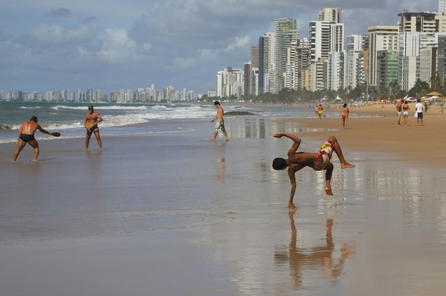 """A youth does a cartwheel on Boa Viagem beach in Recife June 30, 2014. In a project called """"On The Sidelines"""" Reuters photographers share pictures showing their own quirky and creative view of the 2014 World Cup in Brazil. (Photo by Brian Snyder/Reuters)"""