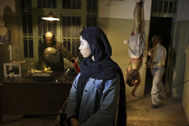 In this January 7, 2019 photo, an Iranian looks at an exhibition at a former prison run by the pre-revolution intelligence service, Savak, now a museum, where wax mannequins of interrogators and a prisoner are displayed, in downtown Tehran, Iran. As Iran marks the 40th anniversary of its Islamic Revolution and the overthrow of the shah, those who suffered torture at the hands of the police and dreaded SAVAK intelligence service still bear the scars. U.N. investigators and rights group say that even today, Iran tortures and arbitrarily detains prisoners. (Photo by Ebrahim Noroozi/AP Photo)