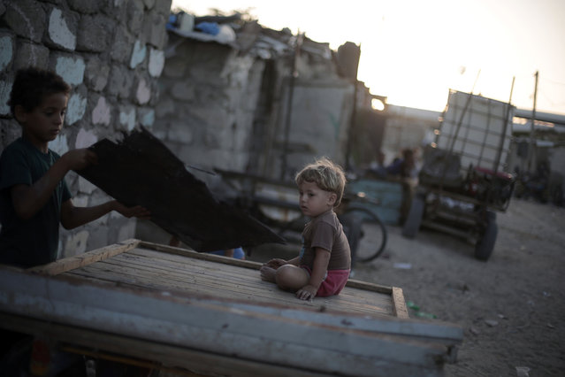 In this Monday, June 20, 2016 photo, Palestinian children play next to their house in el-Zohor slum, on the outskirts of Khan Younis refugee camp, southern Gaza Strip. (Photo by Khalil Hamra/AP Photo)
