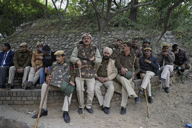 Members of Delhi police sit on a parapet outside the Jawaharlal Nehru University in New Delhi, India, Monday, January 6, 2020. More than 20 people were injured in the attack opposition lawmakers are trying to link to the government. (Photo by Altaf Qadri/AP Photo)