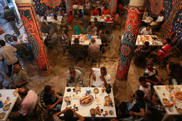 People eat their Iftar (breaking of fast) meal at tables offering free food, set up by a charity, during the holy fasting month of Ramadan in Benghazi, Libya, June 29, 2016. (Photo by Esam Omran al-Fetori/Reuters)