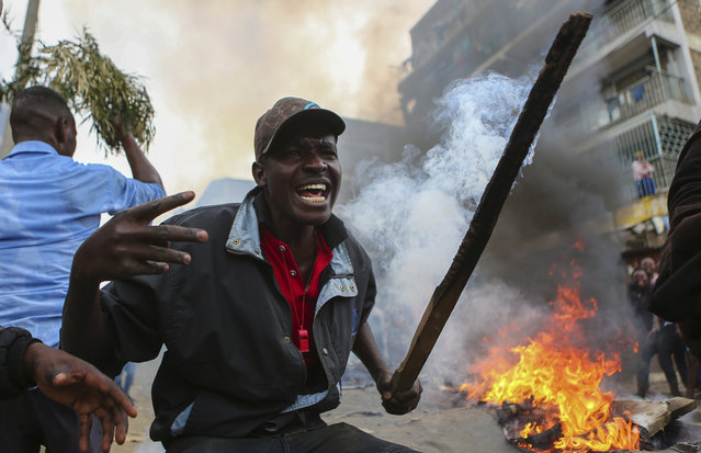Residents of the Mathare area of Nairobi, Kenya, take to the streets by blocking roads with burning tyres to protest in support of Kenyan opposition leader and presidential candidate Raila Odinga, Wednesday August 9, 2017. Odinga alleges that hackers manipulated the Tuesday election results which appear to show President Uhuru Kenyatta has a wide lead over Odinga. (Photo by Brian Inganga/AP Photo)