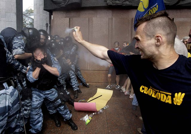Opposition protesters spray tear gas against riot police in front of the Ukrainian House in central Kiev, Ukraine
