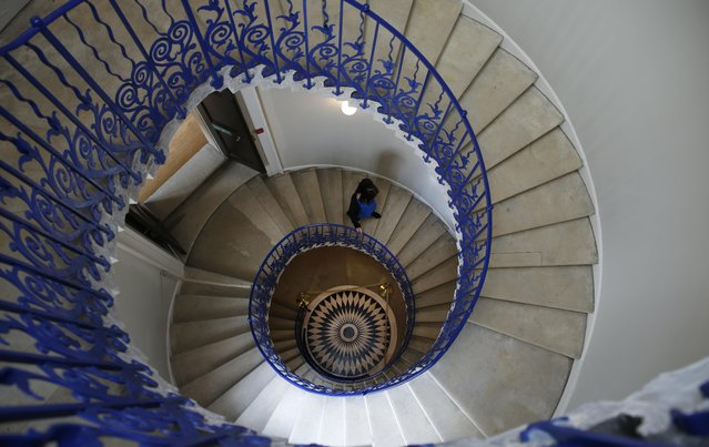 """A member of staff for the Royal Museums in Greenwich walks down the """"Tulip Stairs"""", the first cantilevered stairs built in Britain, at the Queen's House, part of the Royal Museums Greenwich, in London, Tuesday, October 4, 2016. The Queen's House a 17th-century royal villa was the first Classical building in England, designed by renowned architect Inigo Jones, in 1616 for Anne Queen of Denmark, wife of King James I of England and Scotland. (Photo by Alastair Grant/AP Photo)"""