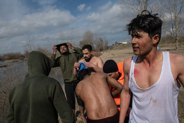 Refugees and migrants rest after they are rescued from an island in the middle of Evros river after becoming stucked for the past two days after trying to cross from Turkey to Greece on March 01, 2020 in Edirne, Turkey. Refugees and migrants from various countries board a boat in an attempt to reach Greece from Turkey by crossing the Evros River on March 01, 2020 in Edirne, Turkey. Thousands of refugees and migrants have flocked to the Greece, Turkey border after Turkey announced that it would open border gates for a period of 72hrs to allow refugees to cross into European countries after thirty three Turkish soldiers were killed in a Syrian air raid in Idlib. (Photo by Burak Kara/Getty Images)