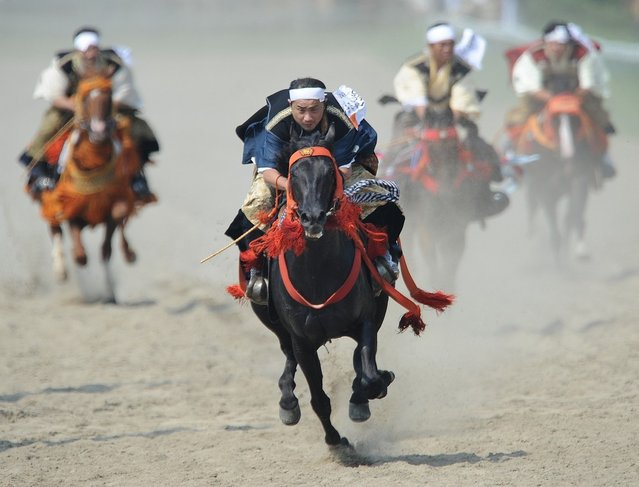 Local people in samurai costumes ride horses during the horse racing at the annual Soma Nomaoi festival in Minamisoma, Fukushima Prefecture, on July 28, 2012.  The traditional full-scale festival kicked off for the first time after the accident of the Fukushima Dai-ichi Nuclear Power Plant following the massive earthquake and the tsunami on March 11, 2011. (Photo by Toru Yamanaka/AFP Photo)