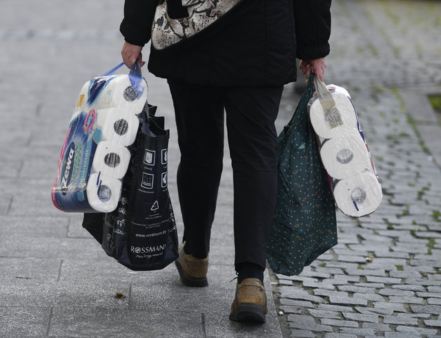 A woman carries her shopping including bags of toilet paper, in downtown Frankfurt, Germany, Wednesday, March 18, 2020. Because of the spread of the coronavirus, bars, cinemas, theatres, museums, and many shops are now closed. (Photo by Arne Dedert/dpa via AP Photo)