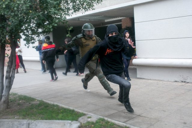 A hooded demonstrator runs away from a riot policeman while demanding changes in the education system in Santiago, Chile, August 27, 2015. (Photo by Pablo Sanhueza/Reuters)
