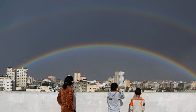 Palestinian children look at a rainbow shining over buildings after heavy rain poured in Gaza City, Thursday, December 12, 2013. (Photo by Hatem Moussa/AP Photo)