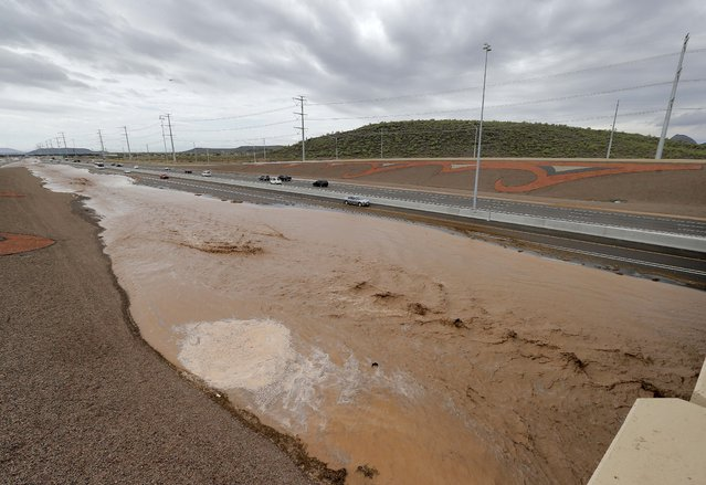 Flash flood waters from the overrun Skunk Creek flood I-10, Tuesday, August 19, 2014, in northwestern Phoenix. Flooding from heavy rain in the Phoenix area has forced authorities to close several major roads, including a portion of Interstate 17 about 25 miles north of the city. (Photo by Matt York/AP Photo)