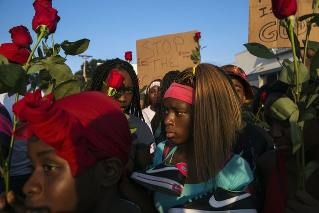 Demonstrators march down West Florissant during a peaceful march in reaction to the shooting of Michael Brown, near Ferguson, Missouri August 18, 2014. Missouri's governor lifted the curfew for the St. Louis suburb of Ferguson on Monday as National Guard troops were called out after days of violent unrest sparked by the fatal shooting of an unarmed black teenager by a white policeman. (Photo by Lucas Jackson/Reuters)