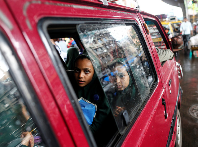 Schoolchildren travel in a car on the way back to their homes, in Mumbai, India, July 18, 2016. (Photo by Danish Siddiqui/Reuters)