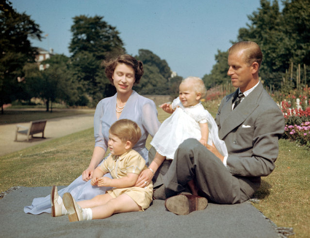 Britain's Princess Elizabeth, later Queen Elizabeth II, Prince Philip and their children Prince Charles and Princess Anne on the lawn at Clarence House, London, August 8, 1951. (Photo by AP Photo/Worth)