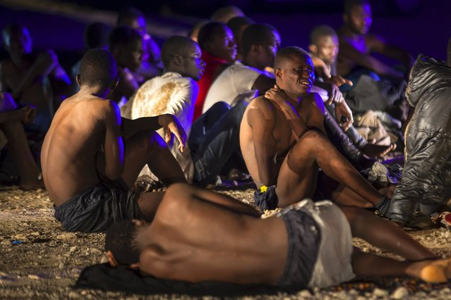African migrants rest after arriving on a fishing boat at Las Carpinteras beach in the Canary Island of Gran Canaria, Spain, September 1, 2015. (Photo by Borja Suarez/Reuters)