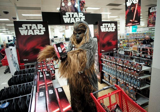 """A fan dressed as Chewbacca selects merchandise from the upcoming film """"Star Wars: The Force Awakens"""" just before midnight on """"Force Friday"""" in Sydney, September 4, 2015. (Photo by Jason Reed/Reuters)"""