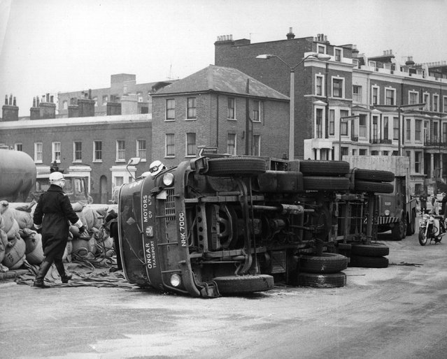 An articulated lorry blocks the main road out of London, the West Cromwell road, after it overturned due to an unstable load, circa 1965. (Photo by Keystone)