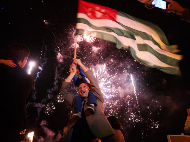"""Abkhaz celebrate on their """"independence day"""" in 2014. Since the war, Abkhazia has been shunned by the international community. But in 2008, shortly after the Russia-Georgia war, Russia formally recognized Abkhazia. Then-Georgian President Mikheil Saakashvili responded that Abkhazia is """"not an internal Georgian problem, or a question of Georgia and Russia. This is now a question of Russia and the rest of the civilized world"""". (Photo by Amos Chapple/RFE/RL)"""