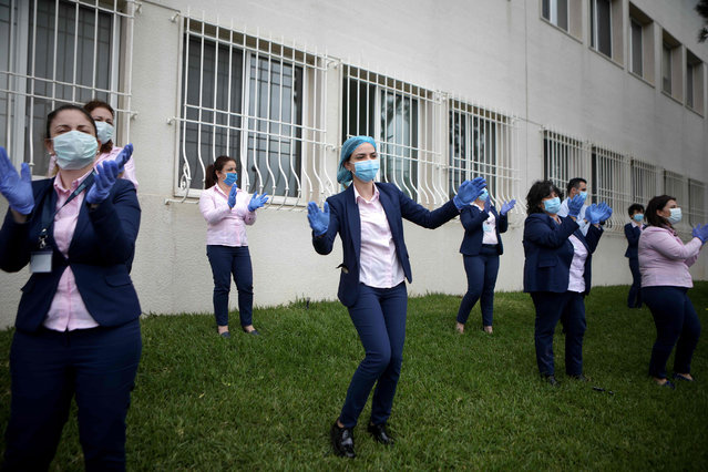 Medical staff members of the Lebanese hospital Notre Dame des Secours dance to music played by a band thanking them for their efforts to support patients during the COVID-19 coronavirus pandemic, in the northern coastal city of Tripoli on April 23, 2020. (Photo by Patrick Baz/AFP Photo)