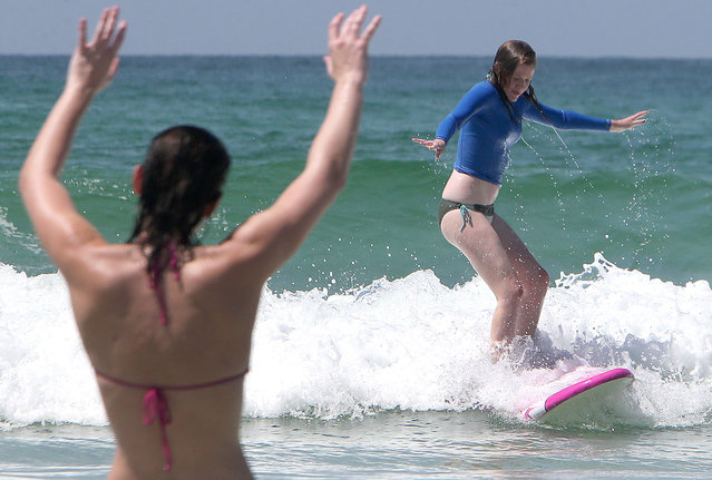 Kaley Flynn cheers on Caitlin Roy as she catches a wave at St. Andrews State Park in Panama City Beach, Fla., on Monday, September 1, 2014. (Photo by Andrew Wardlow/AP Photo/News Herald)