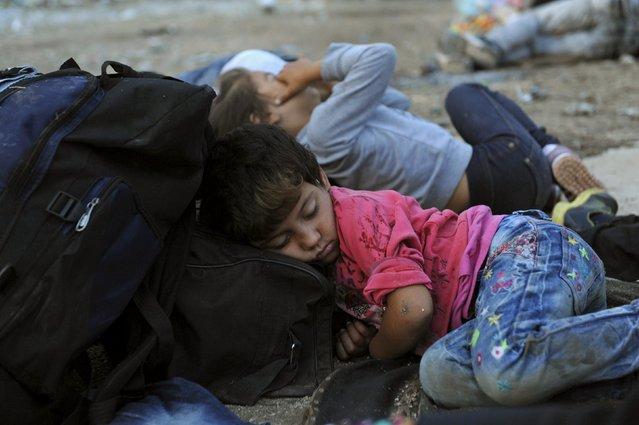 A migrant girl sleeps close to the borders of Greece with Macedonia, near the village of Idomeni, September 6, 2015. (Photo by Alexandros Avramidis/Reuters)