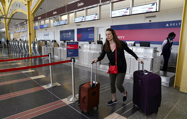 A lone passenger leaves a Delta Airlines counter after checking in for a flight at Reagan National airport as the outbreak of the novel coronavirus (COVID-19) pandemic continues to keep airline travel at minimal levels and the U.S. economy contracts in the first quarter at its sharpest pace since the Great Recession, in Washington, U.S. April 29, 2020. (Photo by Kevin Lamarque/Reuters)
