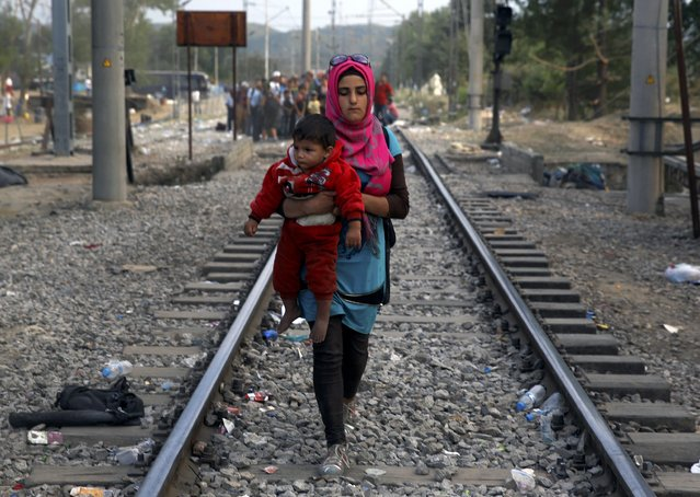 A Syrian refugee carries a baby on her way to cross Greece's border with Macedonia, near the Greek village of Idomeni, September 7, 2015. (Photo by Yannis Behrakis/Reuters)