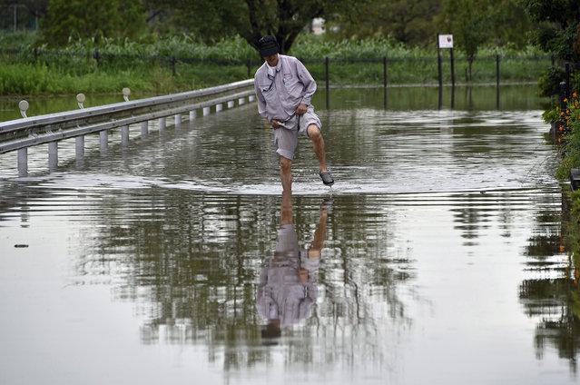 A man walks in a street flooded due to heavy rain generated by typhoon Etau in Koshigaya, Saitama prefecture, north of Tokyo, Japan, 10 September 2015. (Photo by Franck Robichon/EPA)