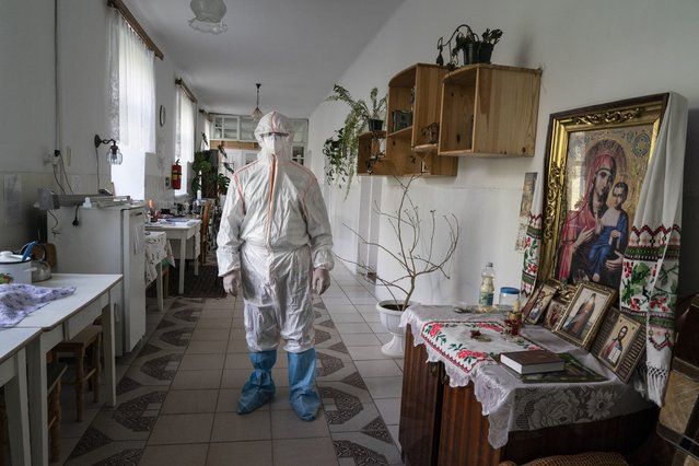 In this photo taken on Friday, May 1, 2020, a medical specialist wearing a special suit to protect against coronavirus, poses for photo next to an icon at a hospital in Pochaiv, Ukraine. Ukraine's troubled health care system has been overwhelmed by COVID-19, even though it has reported a relatively low number of cases. (Photo by Evgeniy Maloletka/AP Photo)
