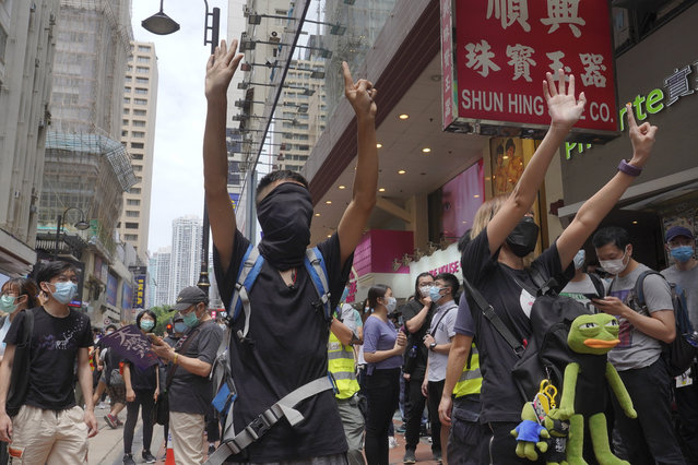 "Protesters gesture with five fingers, signifying the ""Five demands – not one less"" as they march along a downtown street during a pro-democracy protest against Beijing's national security legislation in Hong Kong, Sunday, May 24, 2020. Hong Kong's pro-democracy camp has sharply criticised China's move to enact national security legislation in the semi-autonomous territory. They say it goes against the ""one country, two systems"" framework that promises the city freedoms not found on the mainland. (Photo by Vincent Yu/AP Photo)"