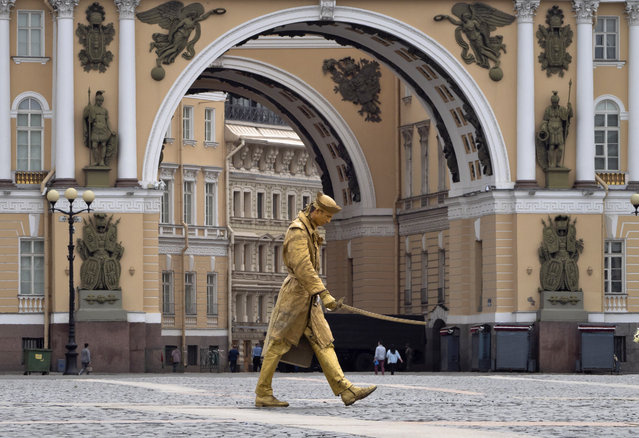 A street actor walks trough the almost empty Palace Square amid the ongoing COVID-19 pandemic in St.Petersburg, Russia, Thursday, May 28, 2020. (Photo by Dmitri Lovetsky/AP Photo)