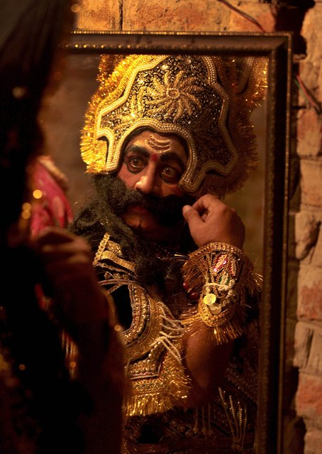 An Indian actor dressed as the Hindu demon king Ravana is reflected in a mirror as he prepares backstage for a performance of the Ramlila, a dramatisation of Hindu God Rama's life, in Jammu on September 25, 2013. Ramlila is a dramatic folk re-enactment of the life of Lord Rama's victory after a ten day battle with the ten headed Demon King Ravana, as described in the Hindu religious epic, the Ramayana. (Photo by AFP Photo)