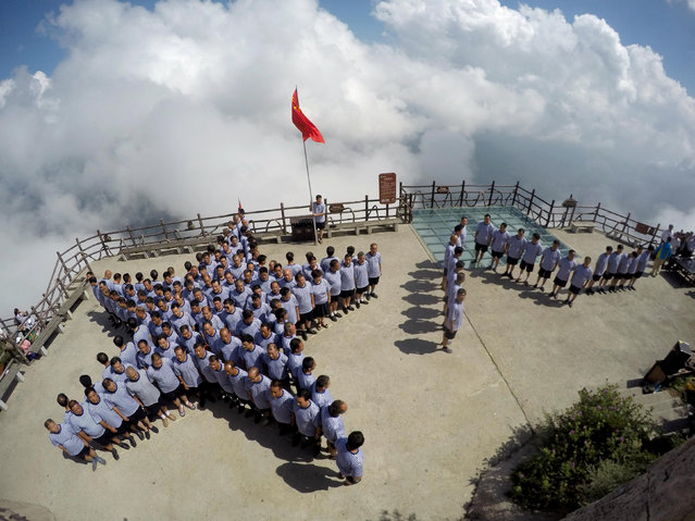 "Veterans of the Chinese People's Liberation army (PLA) navy stand in formation of a star and the Chinese characters ""August 1"" on top of a mountain ahead of China's ""Army Day"" in Luoyang, Henan province, July 31, 2016. (Photo by Reuters/Stringer)"