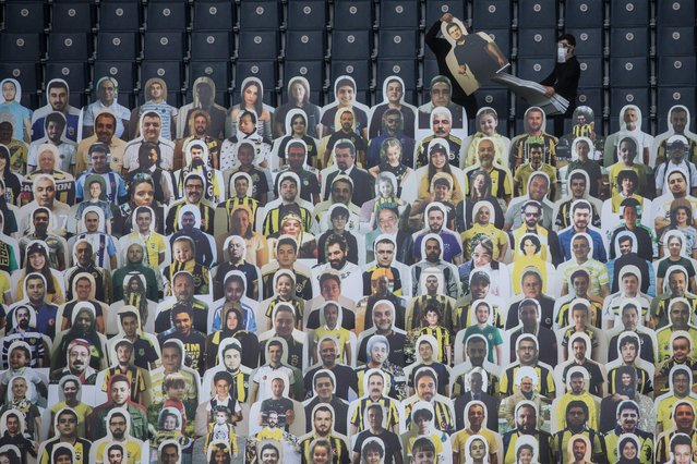 Workers install cut-out portraits of Fenerbahce SK fans at Fenerbahce Sukru Saracoglu Stadium on June 10, 2020 in Istanbul, Turkey. Fenerbahce SK will play Kayserispor in an empty stadium on Friday June 12, in the first Turkish Super League match since the Turkish Football League was cancelled on March 20th due to the coronavirus outbreak. As infection rates of the coronavirus continue to drop and after more than a month of weekend lockdowns, Turkey has begun reopening procedures, allowing bars, restaurants, cafes and some sporting events to begin operations under new restrictions. Limited domestic flights have restarted and the stay-at-home curfew for citizens under 20 and over 65 has been lifted. (Photo by Chris McGrath/Getty Images)