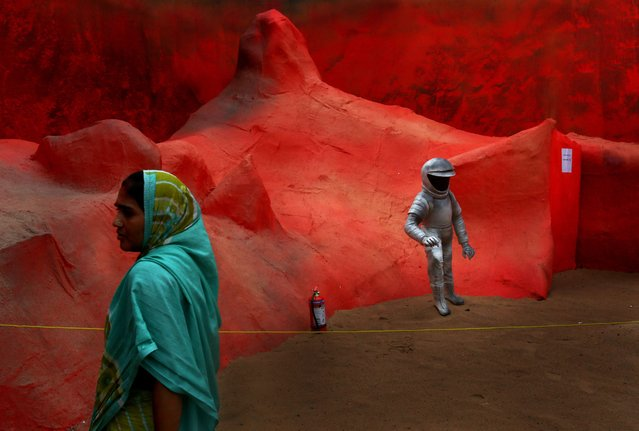 "A woman walks by a pandal art installation entitled ""Mars Mission"" with the figure of an astronaut during the Durga Puja festival in Calcutta, India, 30 September 2014. The Indian Space Research Organisation (ISRO) successfully send an orbiter spacecraft to Mars in September. The Hindu festival of Durga Puja celebrates the killing of a demon king by the goddess. The event runs from 30 September to 04 October. (Photo by Piyal Adhikary/EPA)"