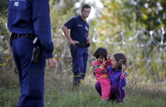 Children guarded by Hungarian police play on the ground after being detained along with other migrants who illegally crossed from Serbia to Hungary near the village of Asotthalom, Hungary, September 16, 2015. (Photo by Dado Ruvic/Reuters)