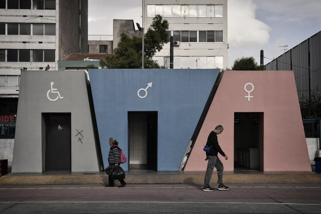 People walk by public toilets at the Port of Piraeus, near Athens, Greece on November 15, 2017. (Photo by Louisa Gouliamaki/AFP Photo)